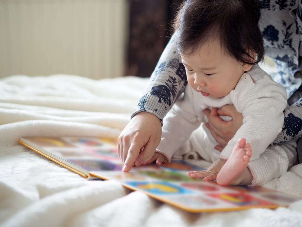 cute baby girl sitting on floor and reading book with mom